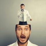 Stressad ung man med den ilskna skrikiga mannen arkivbild