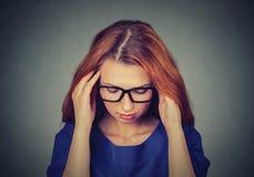 Stressad ung rödhårig manaffärskvinna som har huvudvärk arkivfoto