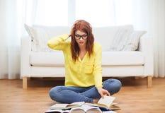 Stressade studentflickaläseböcker hemma Fotografering för Bildbyråer