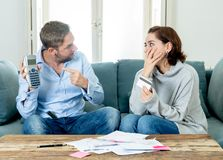 Stressade unga par som har ett argument över betalningar för krediteringsbilskulder och hem- finans royaltyfri foto