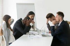 Stressat blandras- lag som tänker av problemlösning på gruppen arkivbild