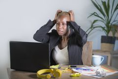 Stressat och frustrerat afro amerikanskt svart kvinnaarbete som förkrossas och förargas på att göra en gest för skrivbord för kon royaltyfri fotografi