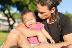 Stressat ut och den frustrerade fadern försöker att trösta hans upprivna litet barndotter från gråt i en parkerainställning royaltyfri fotografi