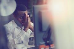 Stressed疲倦了自由职业者有头疼并且认为如何完成他的工作 免版税图库摄影