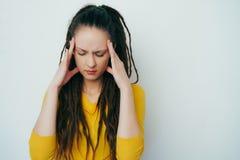 Stressed расстроил красивую девушку с dreadlocks и в желтом ярком свитере напряженно думает, держащ руки на висках  стоковые фото
