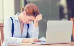 Stressed раздражал потревоженную бизнес-леди сидя перед портативным компьютером стоковая фотография