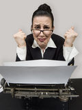 Stressed. Retro business woman at vintage typewriter looking frustrated stock photo