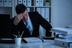 Stressed Accountant Working Late In Office Royalty Free Stock Image