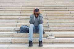Stressed african-american man sitting on stairs Stock Photo