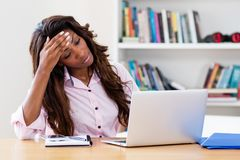 Stressed african american woman at computer. At home at office stock images
