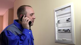Stressed amateur electrician man consulting with colleague specialist on smart phone. Near circuit breaker box cutout at home. Static shot stock video