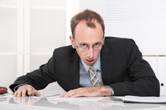 Stressed and angry businessman at desk. Royalty Free Stock Photos