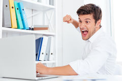 Stressed angry businessman hitting laptop with fist. While sitting at the workplace Royalty Free Stock Image
