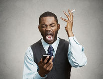 Stressed angry executive holding smart phone and cigarette, scre Royalty Free Stock Photo