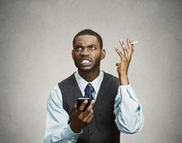 Stressed angry executive holding smart phone and cigarette, scre Royalty Free Stock Photos