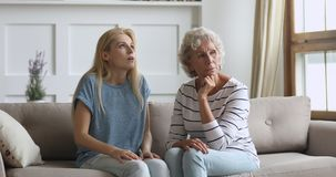 Stressed annoyed young adult daughter argue at stubborn old mother