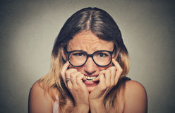 Stressed anxious young woman girl in glasses student biting fingernails Royalty Free Stock Image