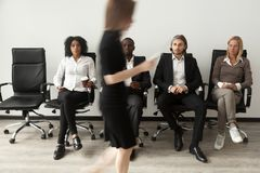 Stressed applicants sitting in queue watching rival after job in. Stressed envious curious applicants preparing for job interview sitting on chairs in queue Royalty Free Stock Photography