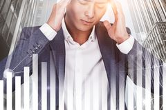 Stressed asian businessman in city, graph stock images