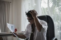Stressed asian businessman holding his head in his hands and Dat. A Charts,business document at office desk Stock Photos