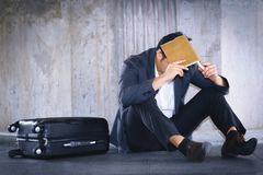 Stressed Asian businessman. A stressed Asian businessman sitting down leaning on the cement wall Royalty Free Stock Photo