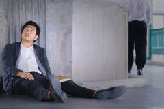 Stressed Asian businessman. A stressed Asian businessman sitting down leaning on the cement wall Royalty Free Stock Photography