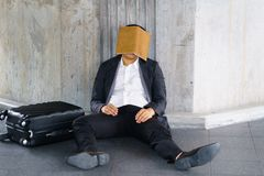 Stressed Asian businessman. A stressed Asian businessman sitting down leaning on the cement wall with cover by notebook Royalty Free Stock Photography