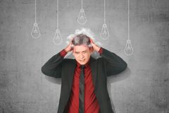 Stressed asian businessman thinking for new creative idea with light bulb hanging. Over gray wall background royalty free stock images
