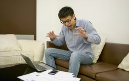Stressed Asian businessman using a laptop in living room at nigh Royalty Free Stock Photography