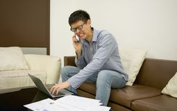 Stressed Asian businessman using a smartphone in living room at Stock Photos