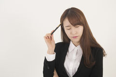Stressed asian businesswoman with a pen Stock Photography
