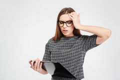 Stressed attractive woman in glassed with clipboard having a headache Stock Photography