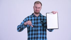 Stressed bearded hipster man showing clipboard and giving thumbs down. Studio shot of bearded hipster man against white background stock video footage