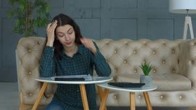 Stressed woman calculating bills and expenses at home. Stressed beautiful long brown hair woman counting bills and expenses while doing domestic accounting in stock video footage