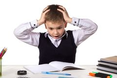 Stressed bewildered pupil sitting at the desk with hands over the head surrounded with stationery.  Stock Photo