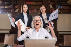 Stressed boss and her female colleagues posing in office. Finishing project. Stressed elderly boss and her young female colleagues posing after working and Stock Images