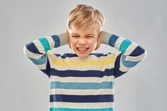 Stressed boy in pullover closing ears by hands royalty free stock photos