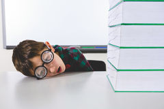 Stressed boy by stacked books on table Stock Images