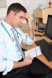 Stressed British GP sitting at desk Stock Image