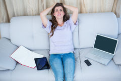 Stressed brunette holding her head on couch Stock Photo