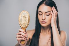 Stressed brunette woman with closed eyes holding hairbrush. Isolated on grey hair loss concept stock photo