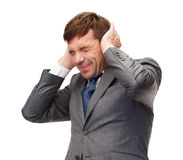 Stressed buisnessman or teacher closing ears Royalty Free Stock Image