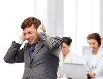 Stressed buisnessman or teacher closing ears Stock Photography