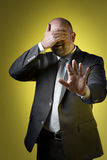Stressed business man. Stressed businessman in dark suit holding up hand in front of his eyes and parries with the other hand, against yellow background Royalty Free Stock Image