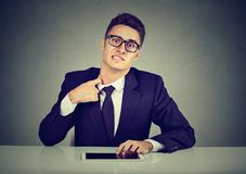 Stressed young business man pulling his shirt on his neck uncomfortable with too tight tie and formal wear royalty free stock images
