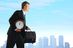 Stressed business man searching for more time. Stressed out business man with a clock under his arm is searching for more time, illustrating overworked corporate Royalty Free Stock Images
