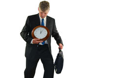 Stressed business man searching for more time. Stressed out business man looking a clock he is holding searching for more time, illustrating overworked corporate Royalty Free Stock Photography