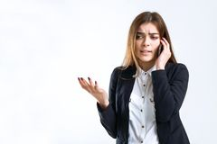 Stressed Business Phone Talk. Cheerful brunette disturbed businesswoman have stressed phone talk on white isolated background with copyspace Stock Images