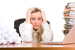 Stressed business woman. A stressed business woman with her head in her hands, sitting at her desk covered a pile of papers and stack of files Stock Photography