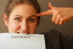 Stressed business woman biting contract Royalty Free Stock Photography